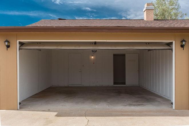 Leere Garage, Garagentor steht offen, Sonnenschein, Garage gehört zu einem Einfamilienhaus. Aaden Wirtschaftsdetektei GmbH Berlin