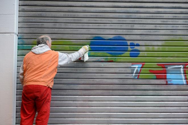 Mann entfernt Graffiti von Tor, Sachbeschädigung in Berlin, Aaden Detektei Berlin