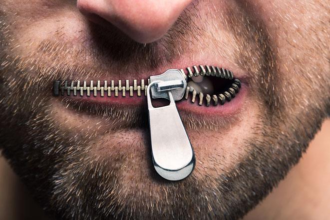 Mann mit teilgeöffnetem Reißverschluss am Mund; Aaden Detektei Köln