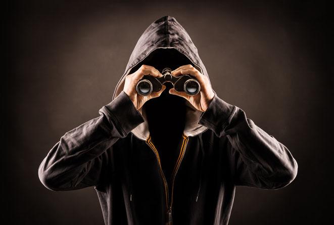 Stalker blickt durch Fernglas. Aaden Detektiv Köln | Stalking Köln | Nachstellung Köln | Privatdetektiv Köln