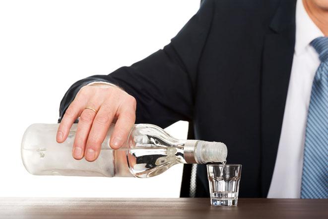 Mann im Anzug schenkt sich Wodka am Arbeitsplatz ein, Aaden Wirtschaftsdetektei Köln