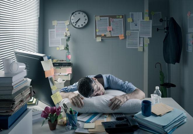 Schlafender Angestellter mit Kissen auf Schreibtisch, Aaden Wirtschaftsdetektei Köln