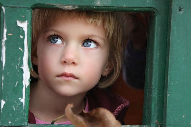 Mädchen schaut aus Fenster