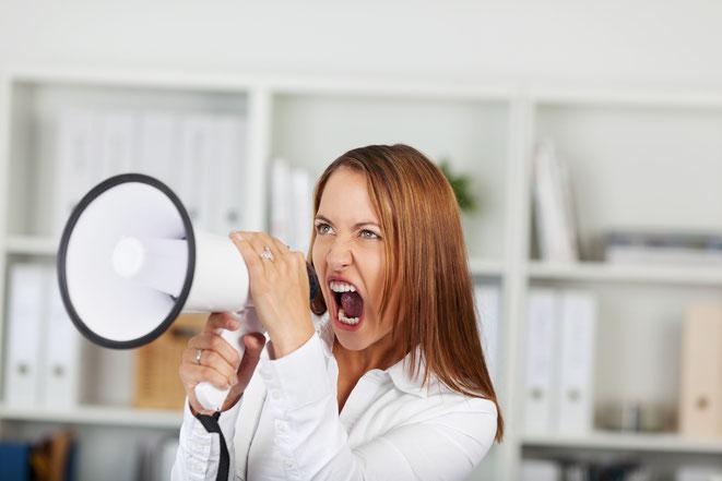 Frau schreit im Büro durch ein Megafon; Aaden Detektei München