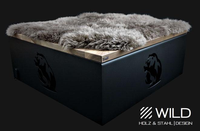 Ein Hocker oder eine Sitzfläche mit Bären und Fell kombiniert mit schwarz mattem Edelstahl und einer massiven Nussholzplatte. Designte Inneneinrichtung von WILD DESIGN.
