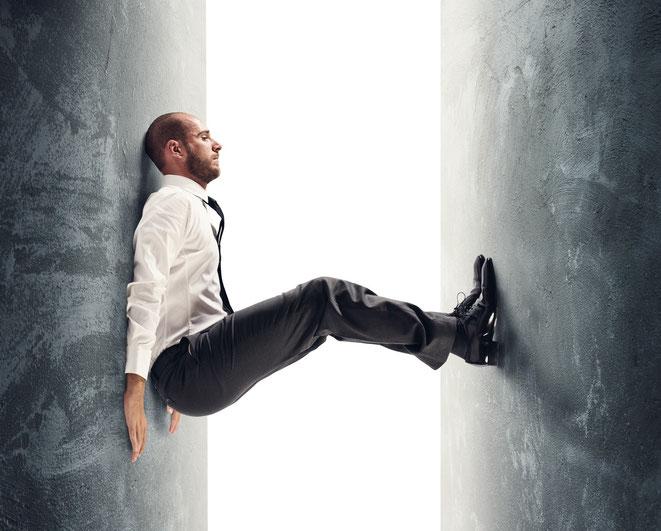 Mann stemmt die Beine gegen eine sich nähernde Wand | Detektiv Hamburg | Wirtschaftsdetektei Hamburg