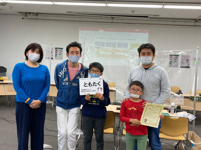 第2日優勝となった「ともたく」の皆さんが、出題の三木智隆さん(左から2番目)と共に記念撮影。中央の小学生のお兄さんが、最後「バイデン」を答え、小学生2倍ルールで大逆転!なんと、アメリカ大統領選挙の様子を毎日熱心に見ていたそうです!