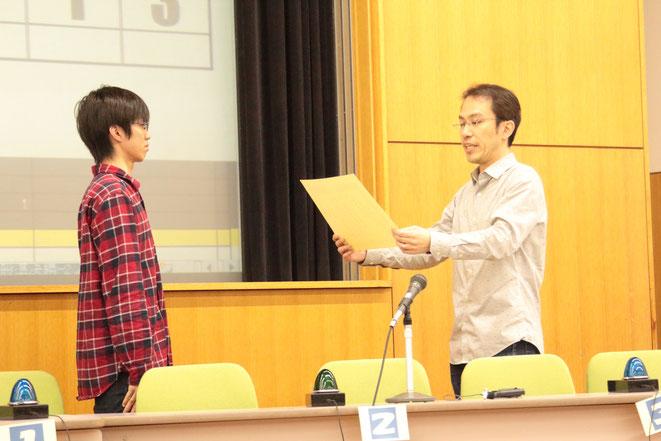 プレAQLジュニアの部優勝の旭丘高校(左)に賞状を渡す、AQL会長(右)