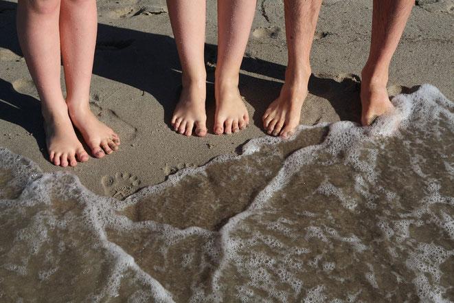 Pies descalzos en arena, olas de mar en playa, huellas de pies en arena