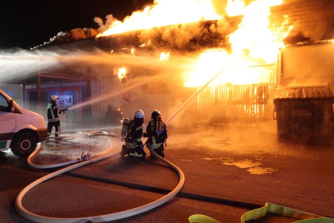 Rechts das Holzlager bei Eintreffen der Feuerwehr in Vollbrand