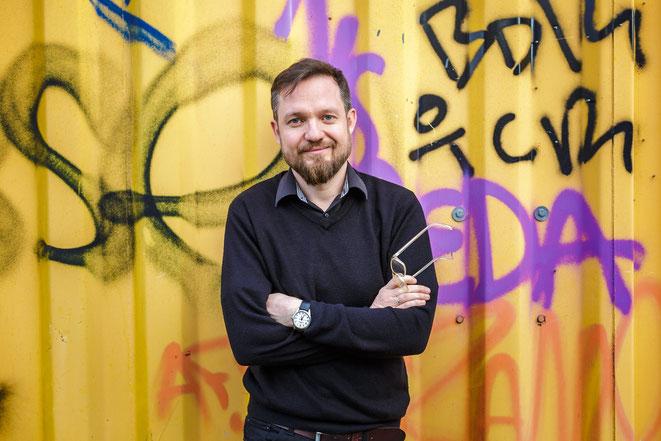 Buchautor und Journalist Simon Hadler vor einem bunten Graffiti.