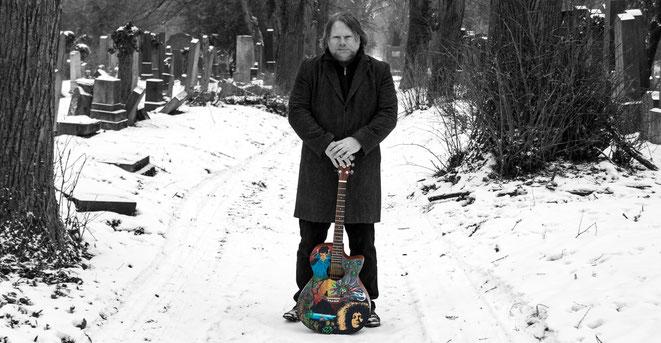 Johann Allacher steht auf einem verschneiten Friedhof und hält eine bunte E-Gitarre.