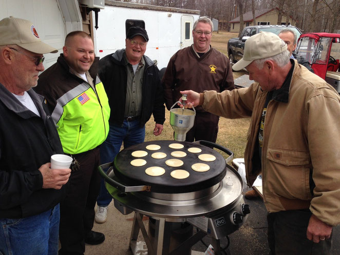 Batter up! Surrounded by members of the club and Cass Cty Sheriff's Department, Lewie Schrupp makes the ceremonial first drop of pancake batter at the Woodtick Wheelers Spring Meeting & Pancake Breakfast. 50 people attended, including many new members.