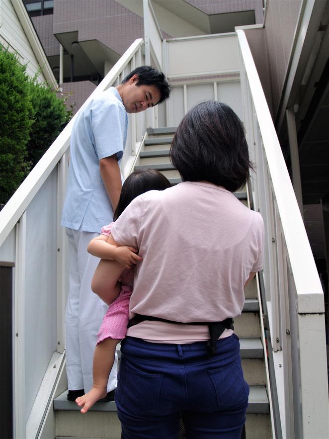 階段を上る赤ちゃんを抱っこした患者さんを見守る。