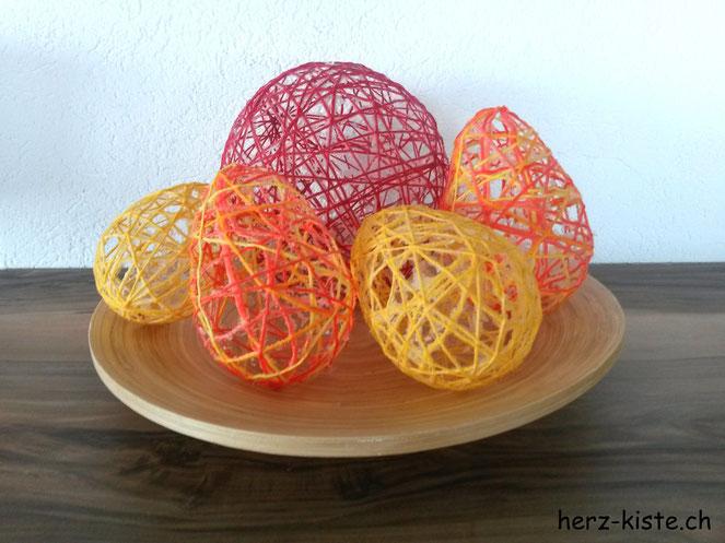 Osterdekoration mit selbstgemachten Ostereiern aus Kleister und Garn mithilfe von Ballonen auf einem Teller präsentiert