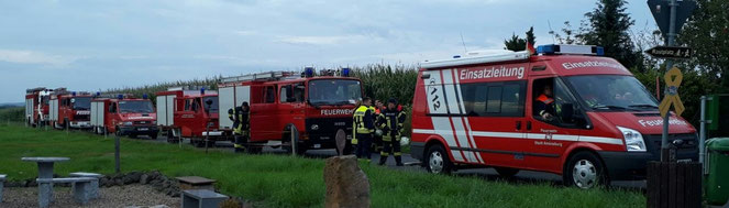 sechs Feuerwehrfahrzeuge, angeführt vom Einsatzleitwagen auf einem Feldweg