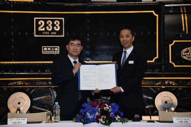 京都鉄道博物館のSL前で行われた締結式(大学提供)森島理事長(右)と三輪正稔JR西日本京都支店長(右)
