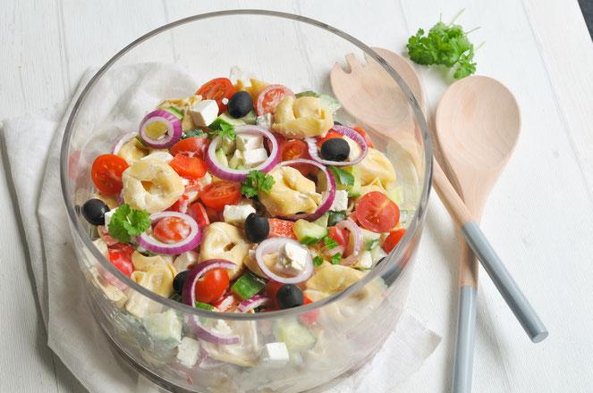 Tortellinisalat griechische Art, mit Tomaten, Zwiebeln, Oliven, Feta etc.