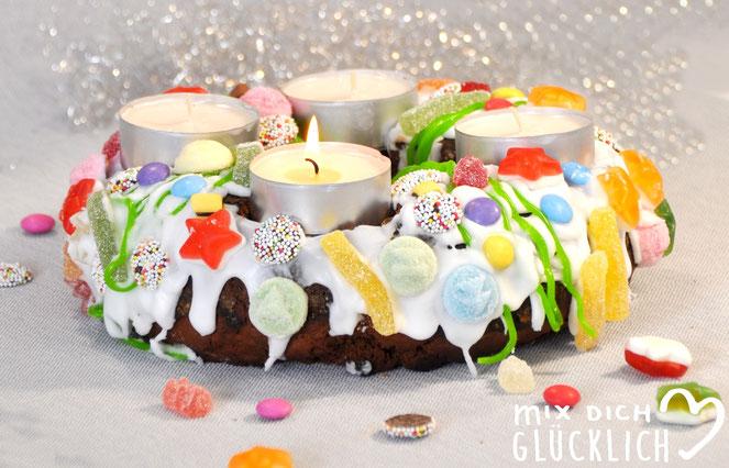 Adventskranz aus Lebkuchen wie Lebkuchenhaus mit Lebkuchenteig Puderzuckerguss und Süßigkeiten als Dekoration