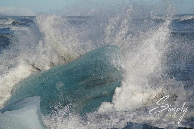Glitzerndes und hellblau leuchtende Eisblöcke in der Brandung des Meeres