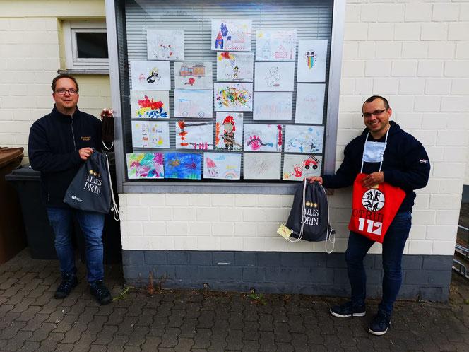 Tobias Rhiel (links) und Damian Plociennik (rechts) stehen neben dem Schaukasten mit den gemalten Bildern