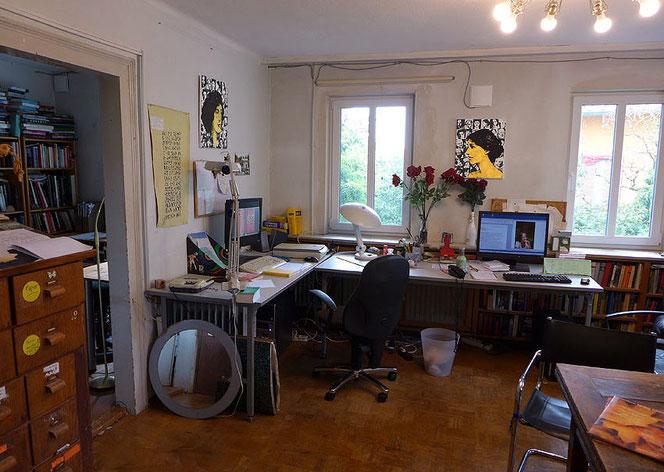Großes Zimmer mit zwei Fenstern, Parkett, großem Eckschreibtisch und zwei PC-Bildschirmen, Magazinschrank aus Holz, an den Wänden Bilder von Virginia Woolf und Vita Sackville-West