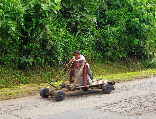 Gesteuert wird mit den Füssen direkt auf die Vorderachse. Zum Bremsen zieht der Fahrer am Hebel und drückt Bremsbacken auf die Hinterräder. Genial einfach.
