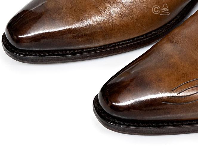 Schuhspitze eines cognacfarbenen Schuhs mit Antikfinish und Wasserpolitur.