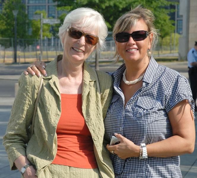 Zwei Frauen in sommerlicher Kleidung lachen in die Kamera: Es sind links Petra-Ines Kaune und rechts die Verlegerin Renate Bach. Beide tragen sonnenbrillen. Renate legt ihren Arm um die Schulter von Petra.