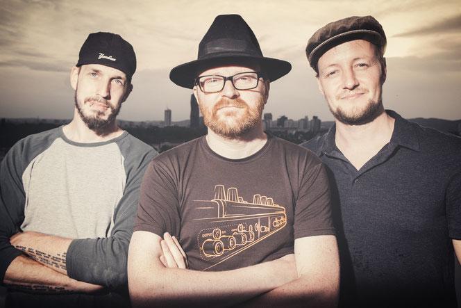 """Philip """" El Fuppo"""" Pflamitzer, Harald Fink und Gregor """"Kujo"""" Kutschera vor Wien Skyline"""