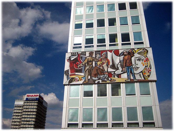 Ein Foto vom haus des Lehrers am Berliner Alexanderplatz. Daneben auf dem Bild ist das Haus des Reisens zu sehen. Bilder und Fotos mit sozialistischer Symbolik aus der DDR.