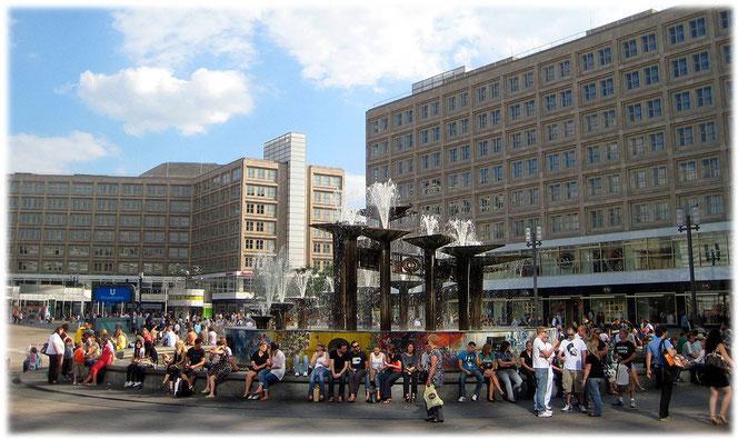 Bilder vom Alexanderplatz in Berlin. Das Foto zeigt den Brunnen der Völkerfreundschaft mit Touristen, Einheimischen und Punks, die auf dem Brunnenrand sitzen. Bilder von der DDR und Ost-Berlin.