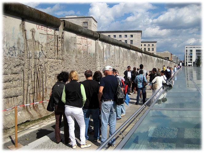 Das Bild zeigt Touristen aus aller Welt, die Fotos und Bilder von den Resten der Berliner Mauer aufnehmen. Rechts sind die Folterkeller der Nazis sichtbar.