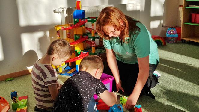 Foto: Erzieherin und Kinder beim Spielen im SOS-Kinderdorf Bernburg
