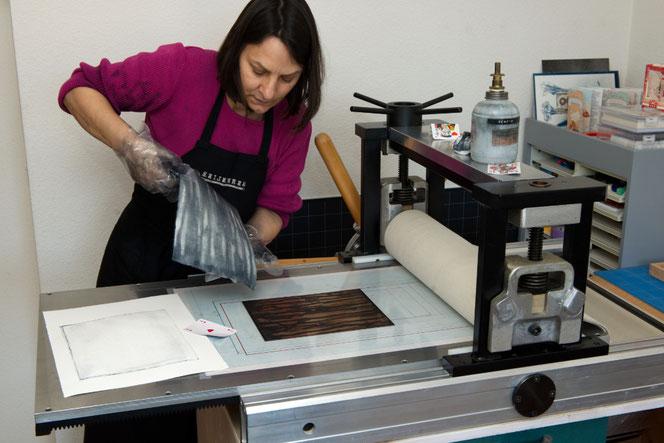 Kupferdruckmaschine - abziehen des bedruckten Blatttes von der Kupferplatte.