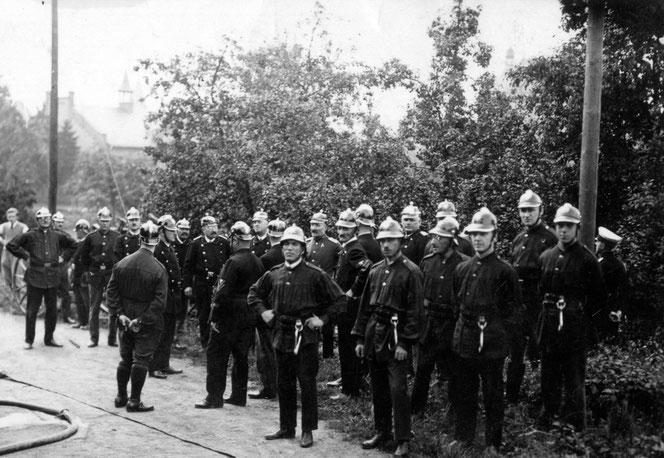 Feuerwehrmänner, um 1930. Im Hintergrund die Turnhalle.