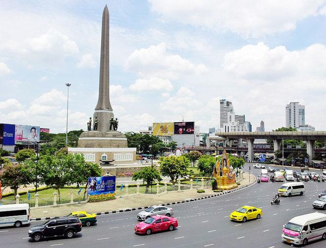 タイ王国・首都バンコク「ビクトリーモニュメント/ Victory Monument Station(BTS)」 駅前の光景。戦勝記念塔が写真奥に、写真手前には道路。車、タクシーなどが走る