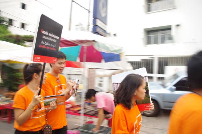 オレンジ色の服を着ている若い男女。募金活動をする学生さんやボランティア団体。手にはプラカードを持っている。チェンマイ サタデーマーケット[タイ・チェンマイ旅行(出張)写真ブログの画像]