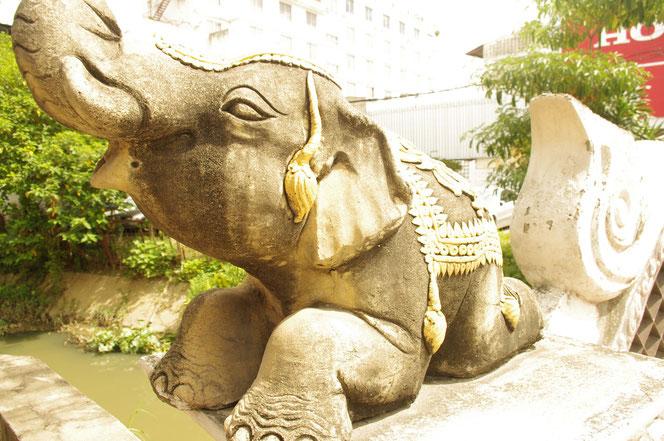 チェンマイにて。橋の脇の手すり部分(欄干)に、石像の象(ゾウ、エレファント)の飾りの写真。タイの雰囲気が出ている。ゾウの石像は伏せ姿で鼻を上げている。表情は穏やか。装飾には金が用いられている。タイ国内では石でできた象も多い。[タイ・チェンマイ旅行(出張)写真ブログの画像]