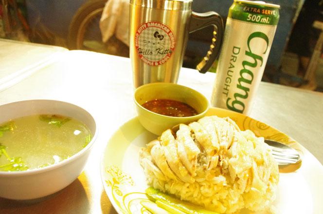 タイ・バンコクで食べたカオマンガイ(海南鶏飯)の写真。テーブルの上にはカオマンガイ、カオマンガイと一緒にサービスで提供されるスープのセット。調味料。タイビールの缶(シルバー色のチャーンビール ドラフト 500ml)とハローキティのステンレスジョッキが [タイ・バンコク旅行(出張)写真ブログの画像]