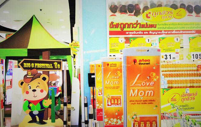 タイ・バンコク(チットロム)のビッグ・シー(Big・C)スーパーマーケット店内にて、タイのお土産を購入した際に撮影。カウボーイ姿の熊のマスコット看板と店内の様子の写真。