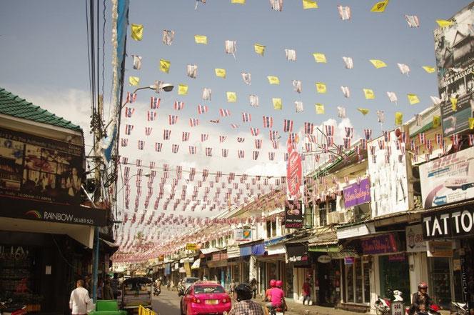 バックパッカーの聖地・バンコク カオサンエリア 数え切れないタイ国旗、タイ王室の旗などが翻る。写真の右側左側は商店。中央には道路。ピンク色のタクシー、ピンク色のバイクにまたがる人も映る【バンコク ピクチャー】  タイ王国の首都・バンコクの旅行(出張)写真ブログ