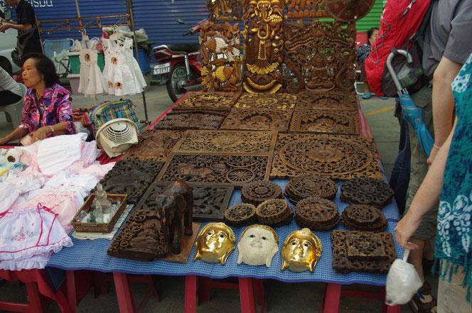 ブッダ(仏像、仏様)の金色の仮面、白色の仮面。また木彫りのレリーフや木彫りの象、木彫りのコースターなどが陳列されている屋台の写真。 チェンマイ サタデーマーケット[タイ・チェンマイ旅行(出張)写真ブログの画像]