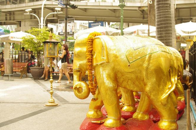 エラワン廟・ブラフマー神の廟の敷地内。タイの神聖な動物「金色の象、ぞうさん、エレファント」のゴールド色の像。お供え物の飾りが首にかかっている。[タイ・バンコク旅行(出張)写真ブログの画像]