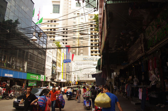バンコクで一番高い超高層ビル、ホテル・バイヨークタワー近辺の雑多な写真。荷物を運ぶ人、tuktukや店舗が映る。電線が空を埋める。
