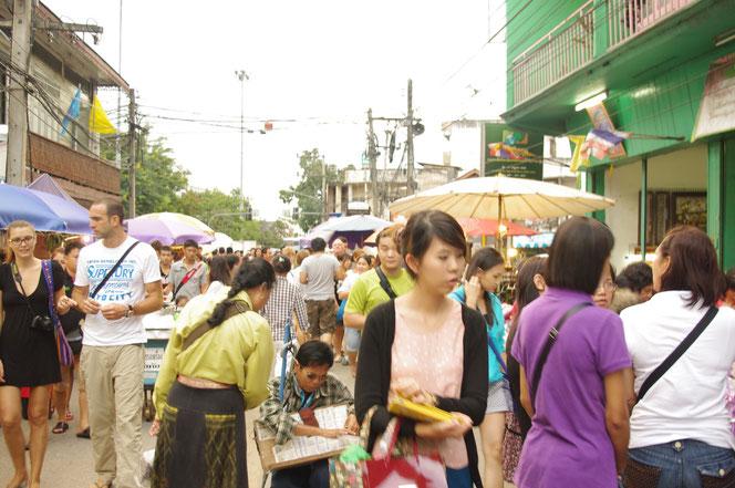 チェンマイサタデーマーケットの夕方の早い時間の歩行者天国の写真。左側に白人さん(タイ語でファラン)の男女カップルの姿。中央には宝くじを売るサングラスをかけたタイ人の男性。[タイ・チェンマイ旅行(出張)写真ブログの画像]