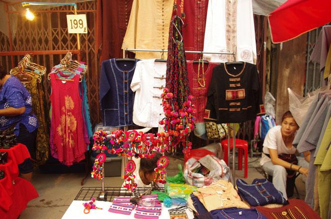 チェンマイ サタデーマーケットの露店 屋台 タイ雑貨屋の商品、モン族?のキーホルダーなど手作り、ハンドメイドの布を用いたピンク色でカラフルな雑貨がディスプレイされている。奥には民族衣装なども売られている。椅子に座るタイ人の女性店主も [タイ・チェンマイ旅行(出張)写真ブログの画像]