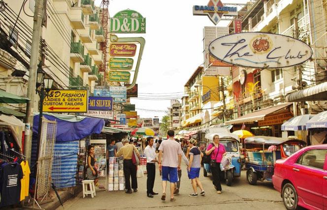 カオサンの道路中央から撮影。欧米人観光客の客引きをする光景。あるく欧米人(白人女性)の後ろにはtuktuk(トゥクトゥク)が。右下にはピンク色のタクシー こちらを見るタイ人の女性。建物が左右に広がる。連なるタイ文字と英語の看板。【バンコク ピクチャー】  タイ王国の首都・バンコクの旅行(出張)写真ブログ
