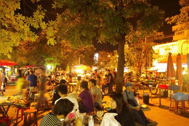 チェンマイ サタデーマーケットを楽しんだ観光客、チェンマイ市民などが屋台街で夕食をしている光景。タイ人男女や外国人の姿。無数のテーブルと椅子が置かれている[タイ・チェンマイ旅行(出張)写真ブログの画像]