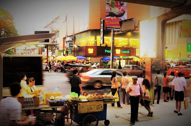 首都バンコクの幹線道路。スクンビット通りの写真。目の前には屋台と行き交う人々。タイ出張旅行時の写真。